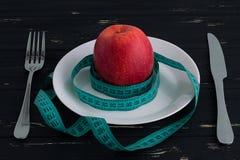 Яблоко на плите с измеряя лентой на деревянной предпосылке Стоковые Изображения