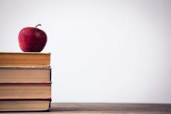 Яблоко на стоге книги на таблице Стоковое Изображение