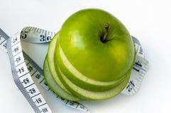 яблоко отрезало измеряя ленту Стоковое фото RF