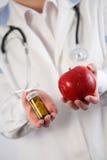 Яблоко против снадобиь в руках доктора. Стоковые Изображения RF
