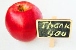 Яблоко с a благодарит вас надпись на предпосылке черноты деревянной доски стоковые фотографии rf