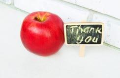 Яблоко с a благодарит вас надпись на предпосылке черноты деревянной доски стоковая фотография rf