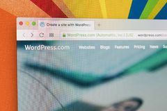 Яблоко iMac с домашней страницей Wordpress на экране монитора под лупой Домашняя страница Wordpress com на компьютере ПК Стоковые Фото