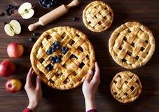 Яблочный пирог на деревянном столе кухни с яблоками и вращающей осью Руки в рамке Традиционный десерт для стоковые изображения