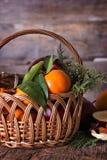Яблоки, апельсины, tangerines, циннамон в корзине Стоковое Фото