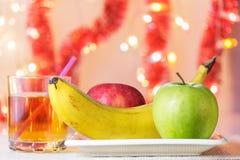Яблоки банана, зеленых и красных на плите и стекле сока Стоковые Фото