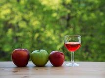 Яблоки бокала красные и зеленые на таблице Стоковое фото RF
