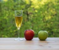 Яблоки бокала красные и зеленые на таблице Стоковые Изображения