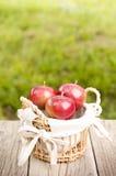 Яблоки в корзине на предпосылке деревянного стола и зеленого цвета Стоковые Фотографии RF