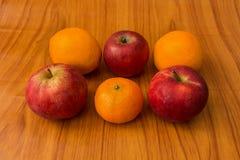 Яблоки и апельсины на коричневой предпосылке Стоковые Изображения