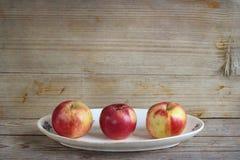 Яблоки на деревянной предпосылке стоковое изображение