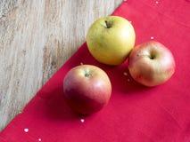 Яблоки на красной ткани Стоковые Фото