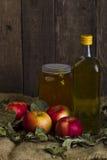 Яблоки с опарником меда и бутылки оливкового масла Стоковые Изображения