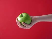 Яблоко в руке на красном цвете Стоковое Фото
