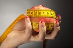 Яблоко диеты с лентой измерения в руке женщины Стоковое Изображение