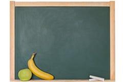 Яблоко и банан перед классн классным Стоковое Изображение