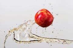 Яблоко и выплеск сока изолированные на серой предпосылке Стоковые Изображения