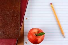 Яблоко и карандаш на бумаге тетради Стоковая Фотография