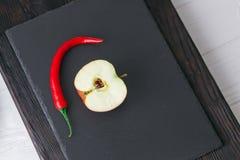 Яблоко и перец на каменной доске Стоковые Изображения RF
