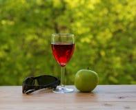 Яблоко и солнечные очки бокала вина зеленые на таблице Стоковое фото RF