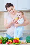 Яблоко младенца молодой матери подавая семья счастливая стоковые фото