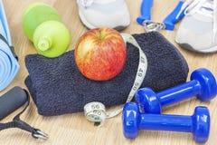 Яблоко на полотенце с оборудованием и рулеткой фитнеса вокруг Стоковое Фото
