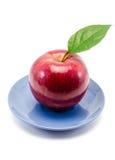 яблоко на синим блюдце 库存照片