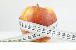 Яблоко окружило измеряя концепцией здоровья и фитнеса ленты стоковое фото