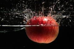 Яблоко падая в воду Стоковое Фото