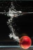 Яблоко падая в воду Стоковое Изображение