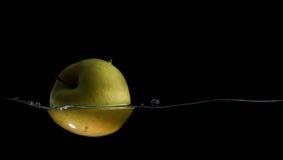 Яблоко при изолированный выплеск воды Стоковые Фото