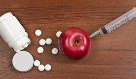 Яблоко с пилюльками медицинскими шприца Стоковые Изображения RF