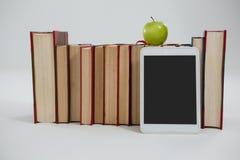 Яблоко, цифровая таблетка и книги на белой предпосылке Стоковое Фото