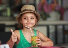 Яблочный сок счастливой девушки ребенк выпивая в ресторане и th показывать Стоковые Изображения RF