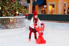 Ягнит катание на коньках в катке парка зимы Конек льда детей на рождестве справедливом Маленькая девочка с коньками на холодный д стоковая фотография rf