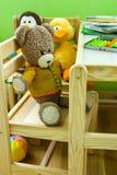 Ягнит комната внутренняя, деревянный комплект мебели, плюшевый медвежонок на стуле, игрушках плюша, книгах, crayons на таблице стоковое фото rf