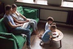Ягнит отпрыски рисуя совместно пока родители используя компьтер-книжку на hom стоковое фото