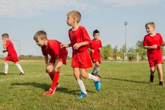 Ягнит футбол футбола - игроки детей работая перед спичкой Стоковые Изображения
