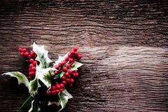 Ягода падуба выходит украшение рождества на старую деревянную предпосылку, винтажный тон Стоковые Изображения