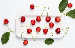 Ягоды вишни и листья вишни на белой верхней части изолированной плитой соперничают Стоковое Изображение