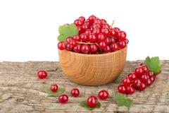 Ягоды красной смородины в деревянном шаре на деревянном столе с белой предпосылкой Стоковые Изображения