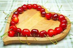 Ягоды сладостной вишни в в форме сердц деревянном шаре в ряд Стоковое Изображение RF