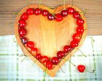 Ягоды сладостной вишни в в форме сердц деревянном шаре в ряд Стоковые Фотографии RF