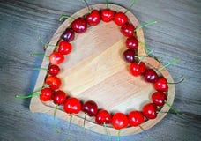 Ягоды сладостной вишни в в форме сердц деревянном шаре в ряд Стоковые Изображения RF