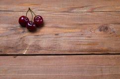 3 ягоды зрелой сладостной вишни на деревянном столе, экземпляре  Стоковое Изображение
