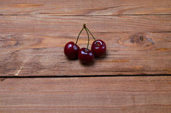 3 ягоды зрелой сладостной вишни на деревянном столе, экземпляре  Стоковая Фотография RF