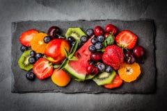 Ягоды и плодоовощи лета ассортимента свежие на черной плите шифера Стоковая Фотография RF