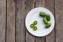 Ягоды кивиа (ледовитое киви) на белой плите на деревянном столе Стоковое Изображение RF