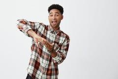 Язык жестов Clos u молодого симпатичного черно-снятого кожу с жизнерадостного парня с афро стилем причёсок в стильной рубашке стоковое фото