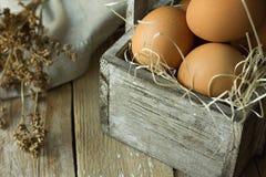 Яичка Брайна органические на соломе в винтажной деревянной коробке на салфетке кухонного стола планки Linen сушат цветки Состав п стоковое изображение rf
